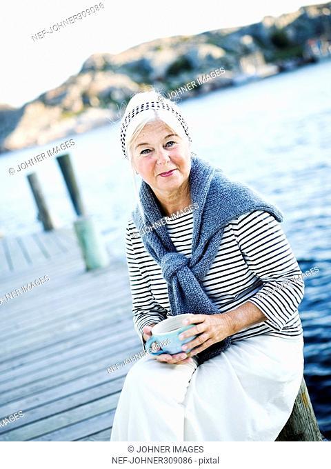 A senior woman drinking tea outside