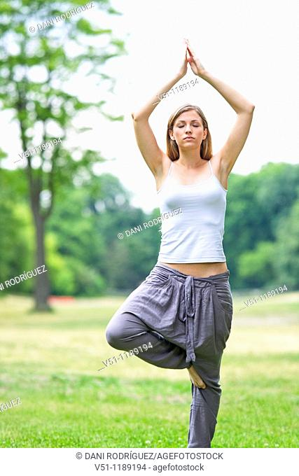Portrait of a blonde woman doing yoga in the park