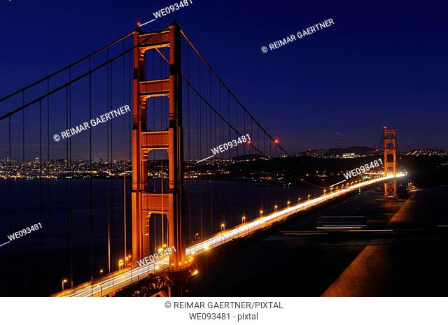 Golden Gate Bridge and San Francisco skyline at night with passing ocean cargo ship