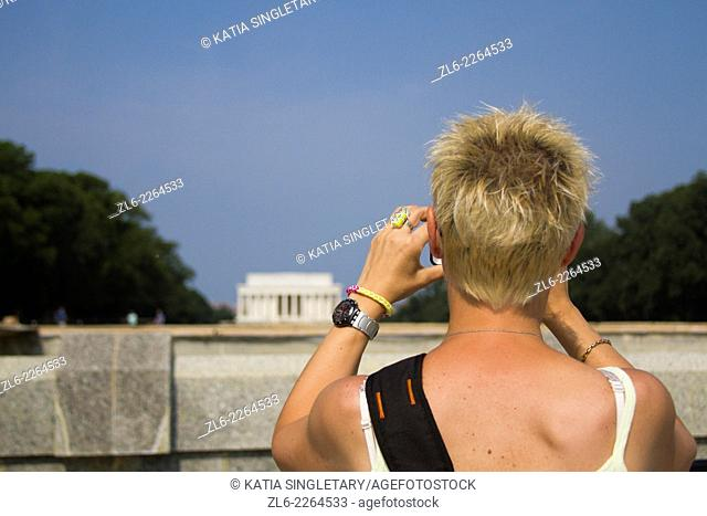 A close up of a caucasian blond woman with short hair in her 40's taking photos of the Memorial in Washington DC on the mall