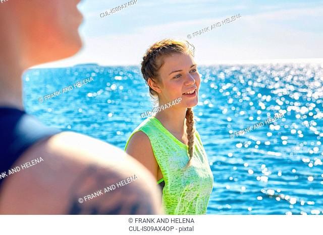 Women with plait in front of ocean looking away smiling