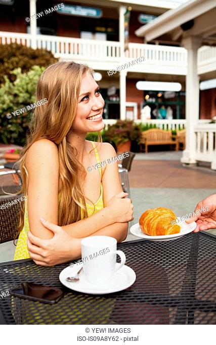 Woman being served croissant
