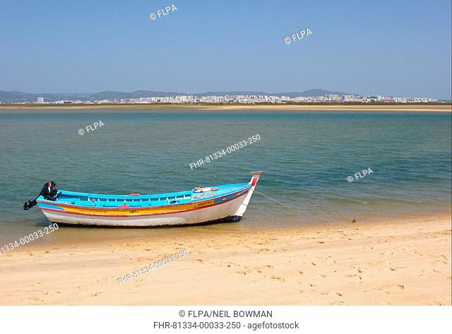 View of city from coastal island with fishing boat, Figo, Algarve, Portugal, april