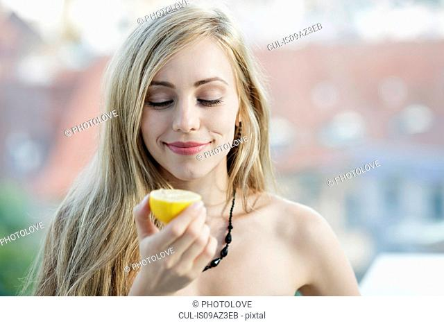 Long haired blond young woman holding a lemon