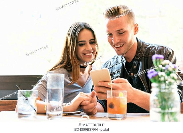 Young couple reading smartphone at cocktail bar table