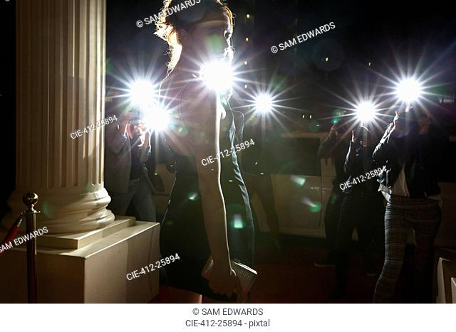 Silhouette of celebrity being photographed by paparazzi photographers at event