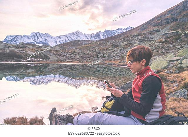Female hiker with phone in hand sitting beside idyllic alpine lake with majestic panoramic view of the italian Alps at sunset