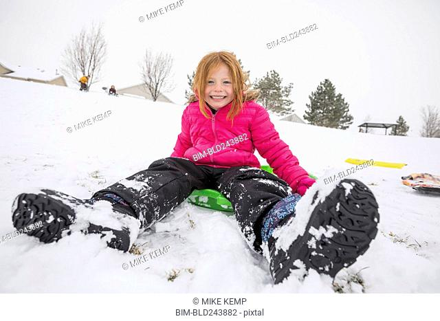 Smiling girl sitting on toboggan in snow