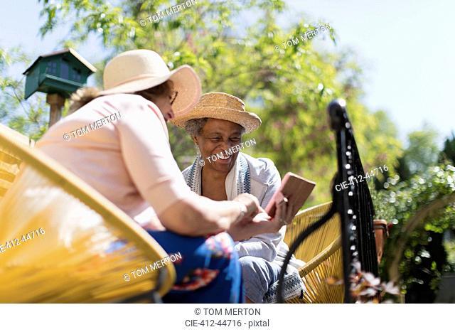 Senior women friends using smart phone on sunny patio