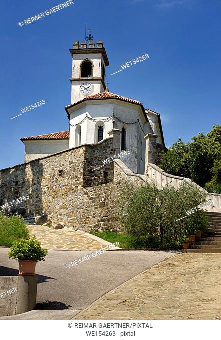 White catholic church of Saint Leonard with chain and clock belfry in Dolnje Cerovo Gorica Hills Brda Slovenia