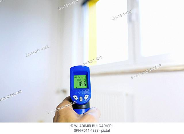 Person holding a digital thermometer