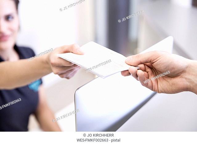 Receptionist handing prescription to patient