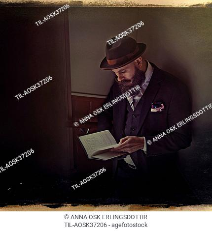 A middle aged male figure with beard wearing a hat and suit reading a book