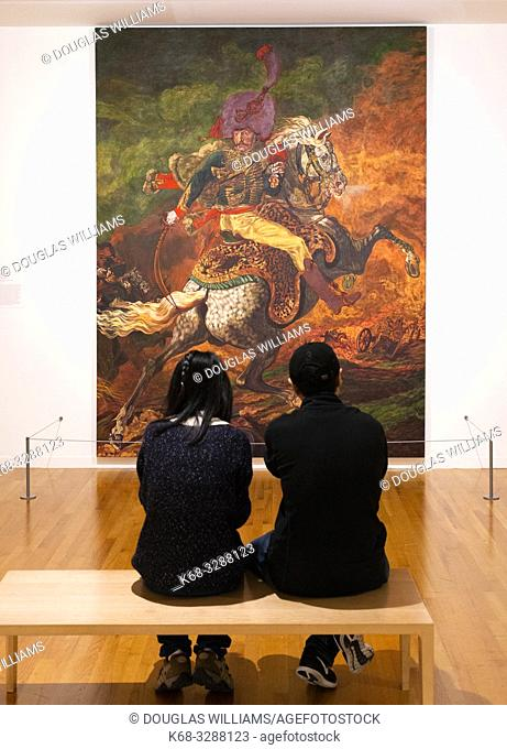 A couple looks at a painting in the Vancouver Art Gallery, Vancouver, BC, Canada
