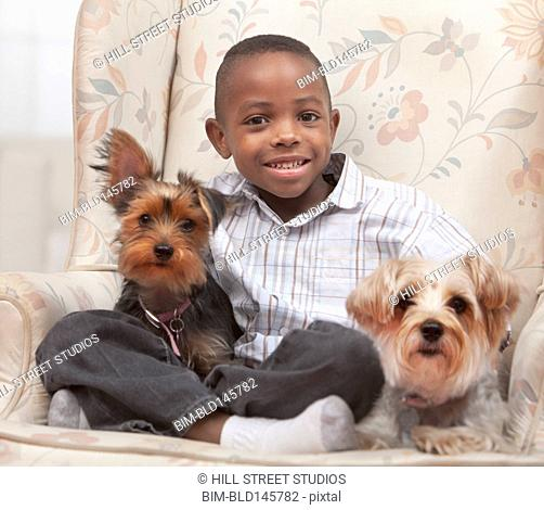 Smiling Black boy sitting in chair with dogs