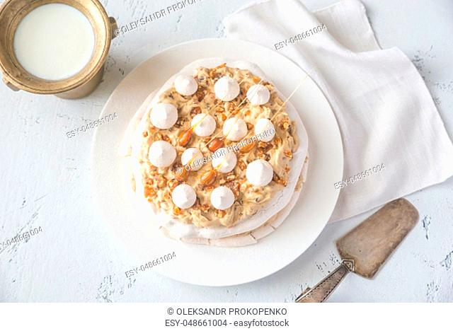 Pavlova cake with caramel and almonds on the wooden background