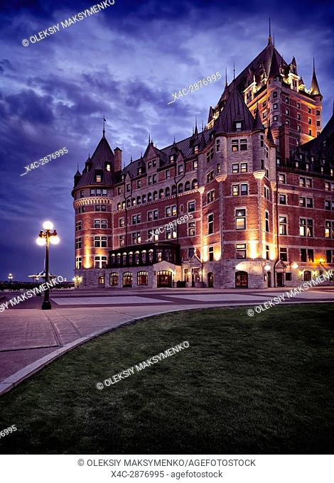Artistic dramatic photo of Fairmont Le Château Frontenac castle illuminated with street lights at night with dramatic nlue sky, grand hotel Chateau Frontenac
