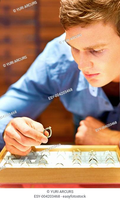 Attractive young man choosing an engagement ring in a jewellery store