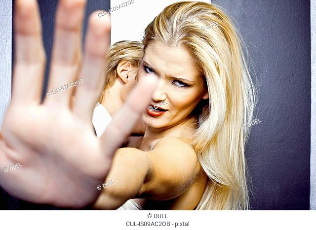 Close up of young angry woman with hand in front of camera