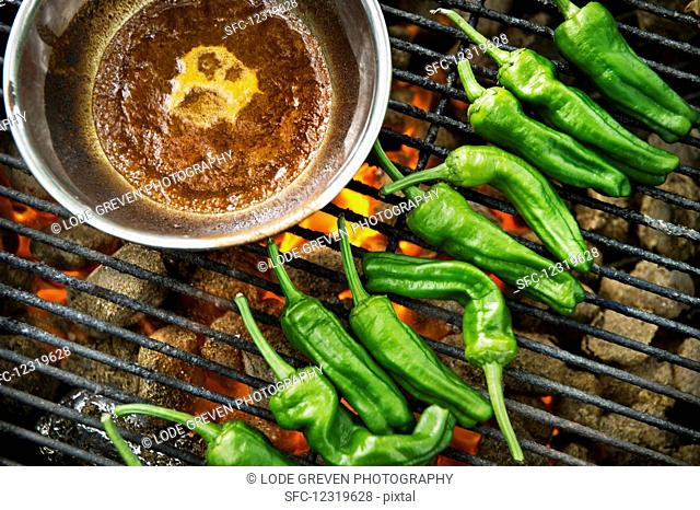 Green chilli peppers on a grill
