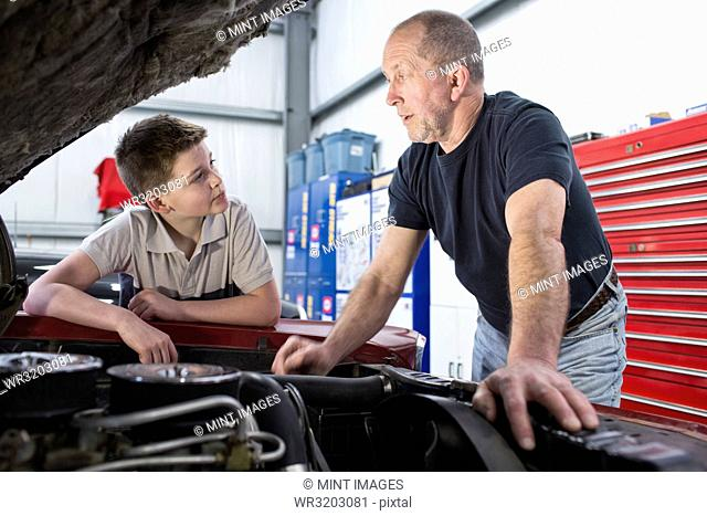 A senior Caucasian male car mechanic showing his grandson how to work on a car engine