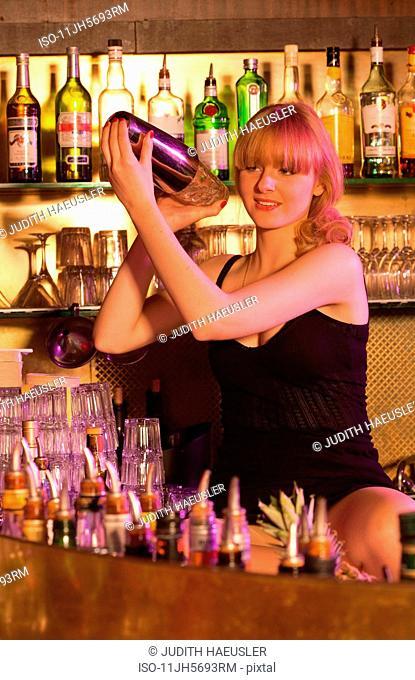 female baarkeeper shaking cocktail