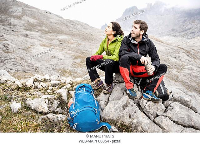 Spain, Picos de Europa, mountaineers resting on rock