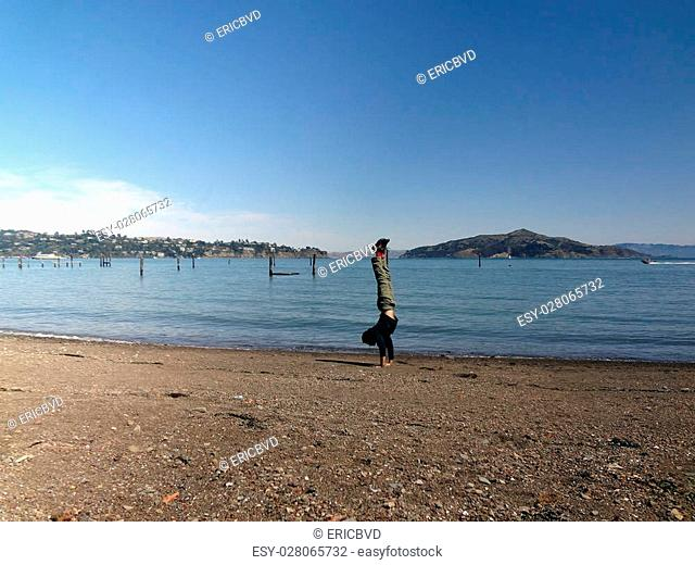 Man wearing a hoodie, pants, and shoes Handstands at on beach in Sausalito is a San Francisco Bay Area city in Marin County