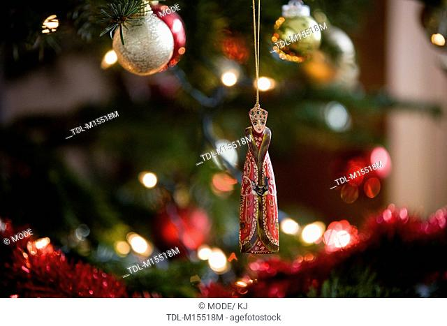 A painted wooden decoration hanging on a Christmas tree