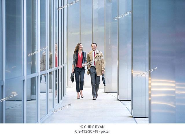 Corporate businessman and businesswoman walking along modern building
