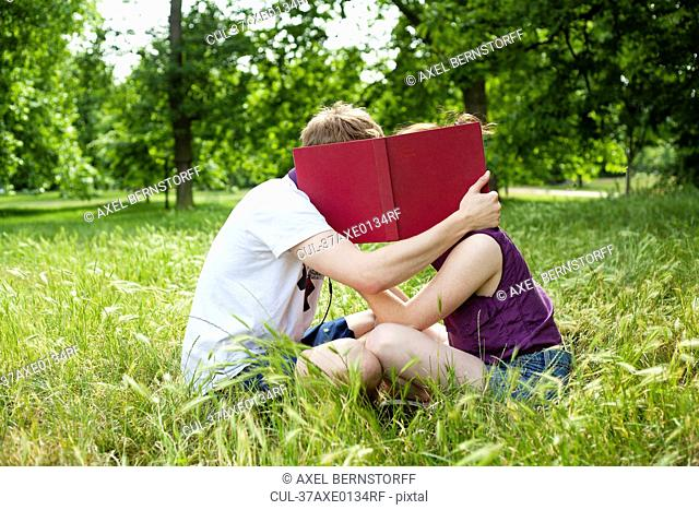 Teenagers hiding behind book in park