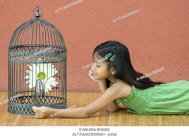Girl opening up birdcage, looking at flower