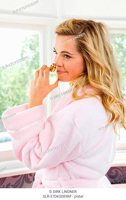 Woman in bathrobe smelling perfume