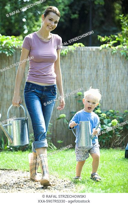 mother with toddler watering plants in garden