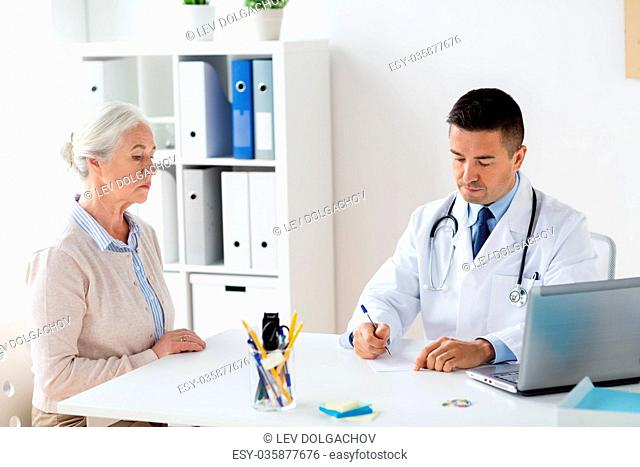 medicine, age, healthcare and people concept - senior woman and doctor with laptop computer writing prescription at hospital