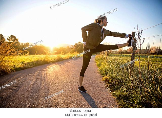 Young woman exercising in rural setting, stretching leg