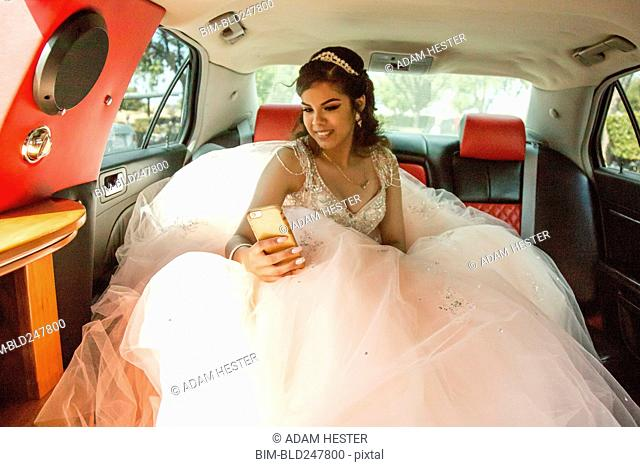 Smiling Hispanic girl texting on cell phone in limousine