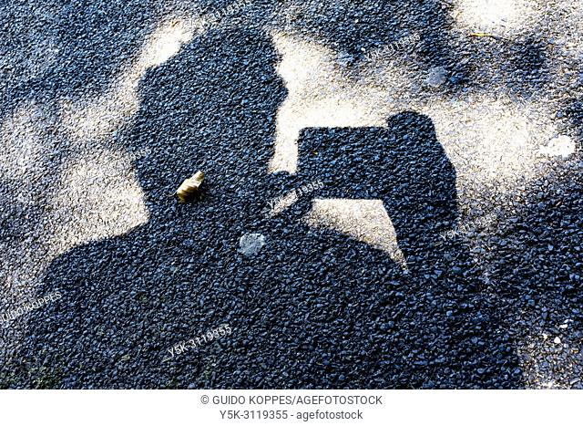 Breda, Netherlands. Self portrait in shadows on the surface of a park's tarmac