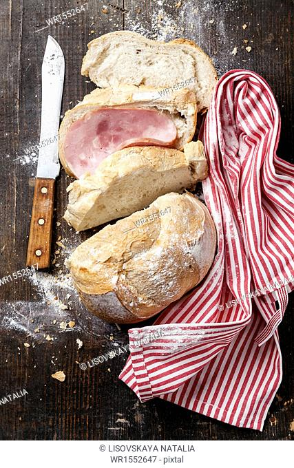 Fresh French bread with ham on wooden background