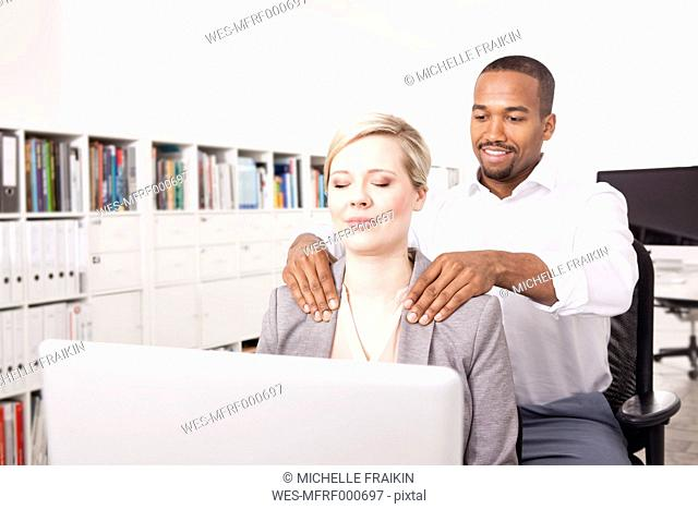 Man massaging his colleague in the office