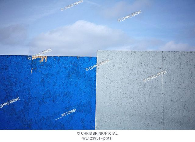 Half blue half grey painted fence on building site in Sandbach, Cheshire, United Kingdom