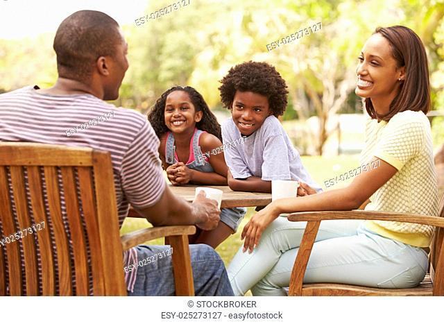 Parents Relaxing Whilst Children Play In Garden