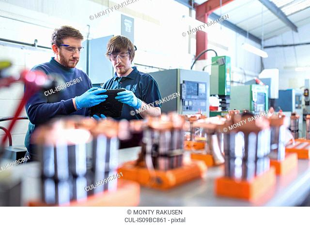 Engineers working with electrodes for electrical discharge machine in precision engineering factory