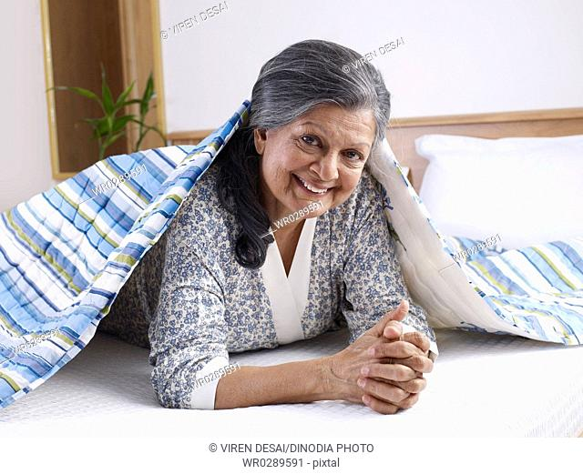 Old lady reclining on bed taking sheet to cover herself MR702S
