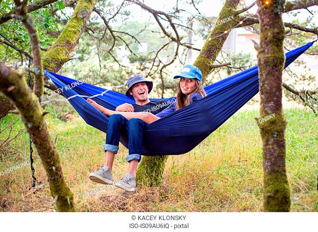 Happy adult couple reclining in blue hammock between trees
