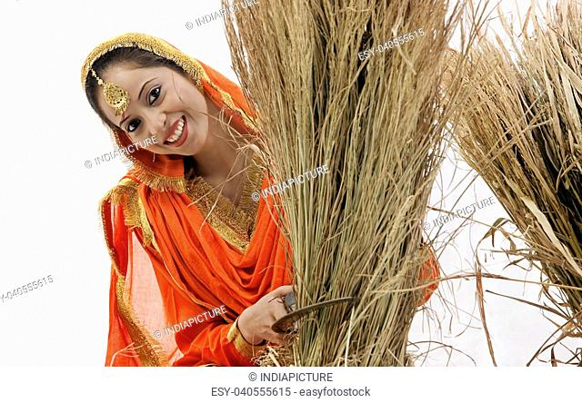 Sikh woman with a sickle and bale of hay