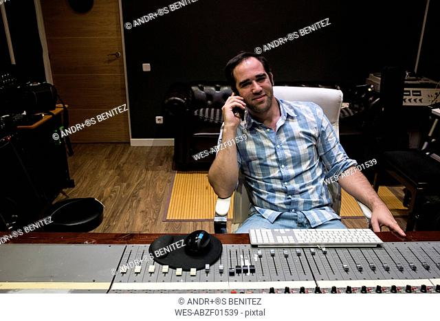 Smiling man in the control room of a recording studio on cell phone