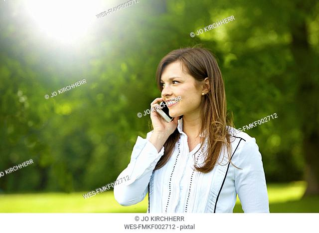 Smiling young woman telephoning with smartphone in a park