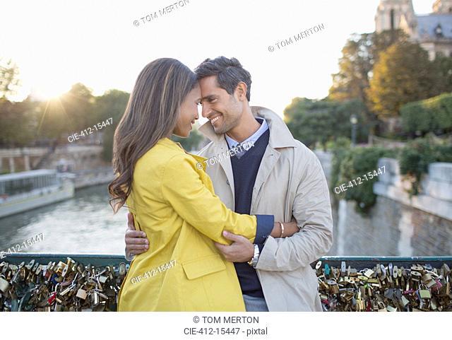 Couple hugging on Pont des Arts, Paris, France