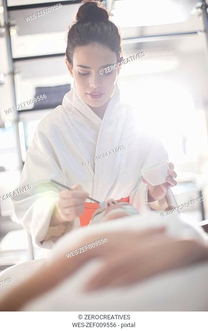 Young woman in spa receiving facial mask